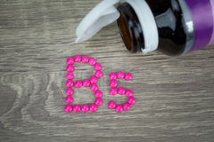 Comprimidos cor-de-rosa que formam a forma ao alfabeto B5 no fundo de madeira Foto de Stock