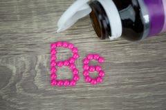 Comprimidos cor-de-rosa que formam a forma ao alfabeto B6 no fundo de madeira Fotos de Stock