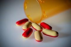 Comprimidos da medicamentação que derramam fora da garrafa fotografia de stock