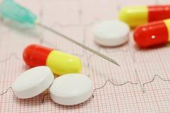 Comprimidos da medicina no cardiogram imagens de stock