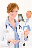 Comprimidos da preensão da mulher nova da equipe do médico Fotografia de Stock Royalty Free