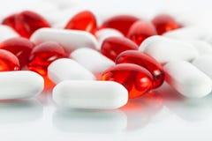 Comprimidos da vitamina: Cápsulas vermelhas e abas brancas imagens de stock