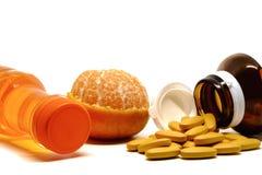Comprimidos da vitamina C, do fruto alaranjado fresco, e da garrafa bebendo doce no fundo branco Foto de Stock