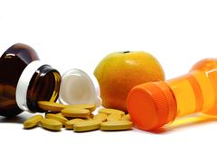 Comprimidos da vitamina C, do fruto alaranjado fresco, e da garrafa bebendo doce no fundo branco Fotos de Stock Royalty Free