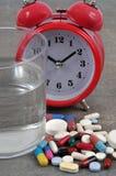 Comprimidos de sono ao lado de um despertador fotografia de stock