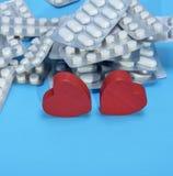 Comprimidos diferentes em um pacote e em dois corações vermelhos Imagens de Stock Royalty Free