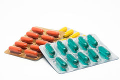 Comprimidos do verde amarelo e das cápsulas de gelatina da laranja no bloco de bolha Fotos de Stock Royalty Free
