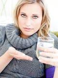 Comprimidos e água deprimidos da terra arrendada da mulher em casa Fotos de Stock