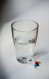 Comprimidos e água no dissipador do banheiro Fotografia de Stock Royalty Free