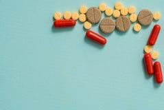 Comprimidos e cápsulas amarelos em um fundo azul Abra a cápsula, medicina pulverizada imagens de stock royalty free