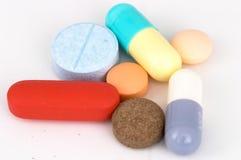 Comprimidos e cápsulas Assorted no fundo branco Foto de Stock Royalty Free