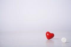 Comprimidos e coração vermelho Fotos de Stock
