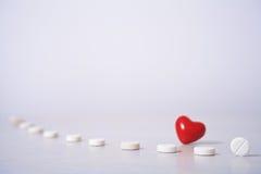 Comprimidos e coração vermelho Imagem de Stock