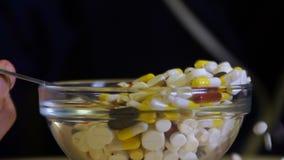 Comprimidos e drogas dos comprimidos de uma colher em uma colher vídeos de arquivo
