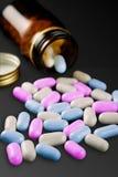 Comprimidos e frasco de comprimido no fundo preto Foto de Stock