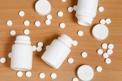 Comprimidos e garrafas em uma superfície de madeira plana fotos de stock royalty free