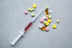 Comprimidos e seringa dispersados Fotografia de Stock