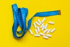 Comprimidos e uma fita de medição em um fundo amarelo, o conceito de peso perdedor imagem de stock