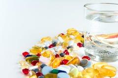 Comprimidos e vidro coloridos da água, no fundo branco Imagens de Stock Royalty Free
