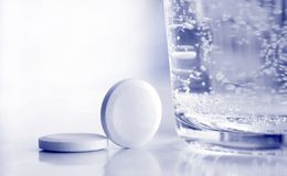 Comprimidos e vidro da água Fotografia de Stock