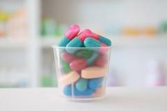 Comprimidos em um copo com drograria Fotografia de Stock