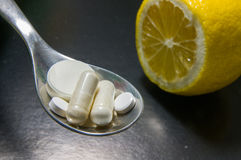 Comprimidos em uma colher contra o limão Imagens de Stock