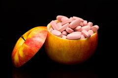 Comprimidos em uma maçã vermelha Fotografia de Stock Royalty Free