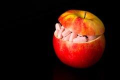 Comprimidos em uma maçã vermelha Fotos de Stock