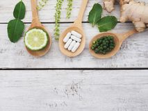 Comprimidos ervais na colher e em ervas de madeira Imagem de Stock Royalty Free