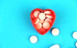 Comprimidos Heart-Shaped O conceito de tratar a doença cardíaca imagem de stock royalty free