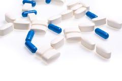 Comprimidos médicos brancos e azuis para tratar doenças em um fundo branco Fotos de Stock Royalty Free