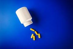 Comprimidos médicos cor amarela e garrafa brilhante Foto de Stock Royalty Free