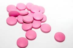 Comprimidos médicos cor-de-rosa no fundo branco Foto de Stock