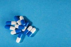 Comprimidos médicos de azul e de branco em um fundo brilhante Fotos de Stock Royalty Free