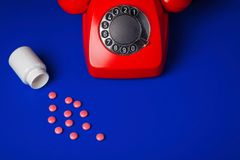 Comprimidos médicos e fundo vermelho do azul do telefone Foto de Stock