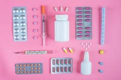 Comprimidos nas bolhas, no termômetro de mercúrio e na seringa em um fundo cor-de-rosa imagem de stock
