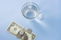Comprimidos organizados ao lado de um copo de água com um dólar e moedas imagem de stock royalty free