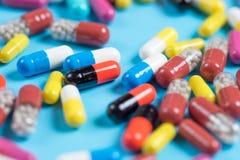 Comprimidos ou cápsulas verdes, amarelas, vermelhas e cor-de-rosa em um fundo azul imagem de stock royalty free