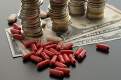 Comprimidos ou cápsulas vermelhas contra notas de dólar e pilhas de moedas imagens de stock royalty free
