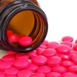 Comprimidos que derramam fora de uma garrafa de comprimido isolada no branco Imagem de Stock Royalty Free