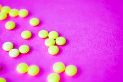 Comprimidos redondos pharmaceptic médicos bonitos da laranja amarela pequena, vitaminas, drogas, antibióticos em um fundo roxo co fotos de stock royalty free