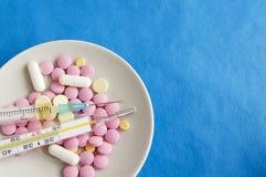 Comprimidos, seringa e termômetro em uma placa medicina Imagem de Stock