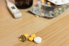 Comprimidos variados na tabela de madeira com comprimidos e xarope do termômetro Imagens de Stock