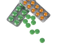 Comprimidos verdes e alaranjados nas bolhas isoladas no branco Fotografia de Stock Royalty Free