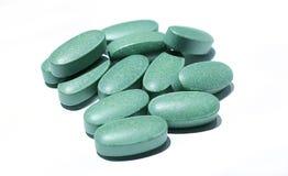 Comprimidos verdes em um fundo branco Foto de Stock Royalty Free