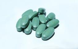 Comprimidos verdes em um fundo branco Imagens de Stock Royalty Free