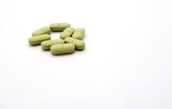 Comprimidos verdes em um fundo branco Foto de Stock