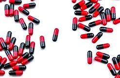 comprimidos Vermelho-pretos da cápsula espalhados no fundo branco Uso da droga antibiótica com razoável Indústria farmacêutica ph imagem de stock royalty free