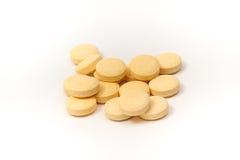 Comprimés jaunes avec le fond blanc Photo libre de droits