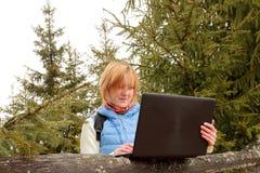 Comprobación de correos en bosque con el ordenador portátil Imágenes de archivo libres de regalías